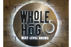 Whole Hog Metallic LED Sign <br/> Metallic, back surface, Raised acrylic logo using edge lit and backlit LEDs, Halo lighting effect around outside of sign